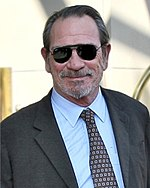 Photo of a smiling Caucasian male in his early sixties who is wearing sunglasses, a grey suit, a blue shirt, and a black tie with grey squares and black circles.