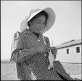 Topaz, Utah. Knitting warm woolen clothing for her children against the coming winter, this Japanes . . . - NARA - 538698.tif