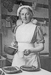 Photographie monochrome de Turner en tablier et chapeau de cuisinier.  Elle tient une casserole et une tasse à mesurer.  Sur une table devant elle sont plusieurs flans, toujours dans leurs plats en métal
