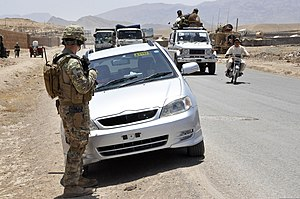Urozgan Province - U.S. Army soldier watching Afghans pass during a logistics inspection in Tarinkot.