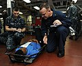 U.S. Navy Chaplain Lt. Gregory Peters and Religious Specialist 2nd Class Michael Frongello speak with a simulated injured victim in a mass casualty training exercise aboard the aircraft carrier USS George H.W 130521-N-CZ979-194.jpg