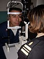 US Navy 040128-N-8861F-003 Hospital Corpsman 2nd Class Jamie Zhunepluas from Queens, N.Y., gets a slit lamp eye exam by Lt. Cmdr. Jacqueline Pierre from Shelbyville, Texas.jpg