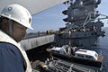 US Navy 040615-N-4533L-048 Boatswain's Mate 1st Class William Lester from Atlanta, Ga., ensures the safe lifting of the admiral's barge from the hangar bay aboard USS Enterprise (CVN 65).jpg