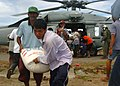 US Navy 050113-N-8629M-162 Victims of the Southeast Asian tsunami anxiously grab supplies delivered by an MH-60S Knighthawk helicopter from Helicopter Combat Support Squadron Five (HC-5).jpg