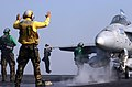 US Navy 050301-N-2984R-094 An Aviation Boatswain's Mate prepares to guide an F-A-18C Hornet to a catapult as a squadron troubleshooter leaps to get an eye-level view of the top of a wing during final checks.jpg