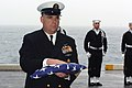 US Navy 061213-N-5248R-014 USS Theodore Roosevelt (CVN 71) Command Master Chief (CMC) Christopher Engles render honors by receiving the National Ensign for the family of the deceased during a burial at sea.jpg