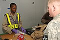 US Navy 061223-N-5758H-113 Storekeeper 3rd Class Natasha Ogarro, assigned to Navy Customs Battalion Romeo, inspects and searches the belongings of a soldier to ensure his luggage is contraband free at an air base in Southwest A.jpg