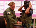 US Navy 091021-N-0535P-031 Naval Air Crewman 2nd Class Mehgan Rodriguez, assigned to Pacific Missile Range Facility, Kauai, Hawaii, helps a student try on aviation survival equipment during a career fair at Waimea Canyon Middle.jpg