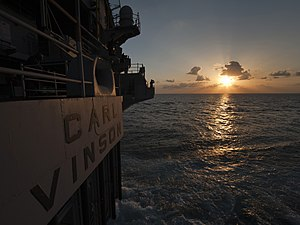 US Navy 120131-N-DR144-843 Seaman Matthew Haag stands watch as a lookout at sunset on the fantail aboard the Nimitz-class aircraft carrier USS Carl.jpg