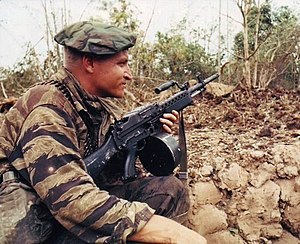 Stoner 63 - A Navy SEAL in Vietnam keeps his Stoner 63 light machine gun at the ready while the rest of his squad prepares demolition charges on a Vietcong bunker. The weapon is fitted with a 150-round drum belt container and is fed from the left-hand side. The retracting handle is locked forward and the ejection port closed with a dust cover to minimize dirt entry.
