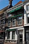 foto van Huis met schilddak en lijstgevel, beganegronds gebosseerd gepleisterd, daarboven schoon werk
