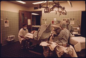Maternal mortality in the United States - Image of a woman about to give birth in the delivery room of Loretto Hospital in New Ulm, Minnesota. The mother is on her back with her legs spread across, two hospital attendants in on the right, her husband on the left, and everyone is wearing a facemark and hospital gown. Industrial equipment are in the room with a light above the mother.