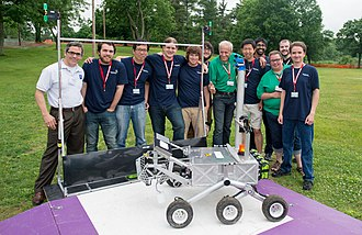 Centennial Challenges - The West Virginia University Mountaineers pose with their robot, Cataglyphis, and officials at the 2014 NASA Centennial Challenges Sample Return Robot Challenge at Worcester Polytechnic Institute in Worcester, Mass., after completing Level 1 for a prize of $5,000. A year later, the team won the $100,000 Level-2 Prize. In 2016, Team Mountaineers won the final challenge with a $750,000 prize (NASA/Joel Kowsky)