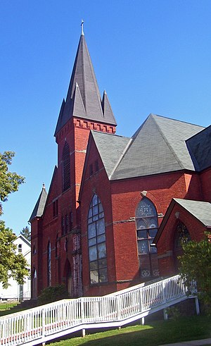 A red brick church with several peaked black towers and a white wooden wheelchair ramp in front