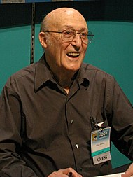 An bald elderly man in a brown shirt.