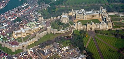 An aerial photograph of Windsor Castle, with three walled areas clearly visible, stretching left to right. Straight roads stretch away in the bottom right of the photograph, and a built-up urban area can be seen outside the castle on the left.