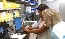 Pharmacists filling prescriptions at a computer
