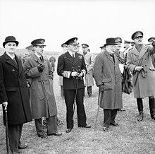 Churchill wordt omringd door mannen in uniform.  Lord Cherwell draagt een bolhoed.