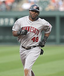 "A dark-skinned man running in a grey pinstriped baseball uniform with ""MINNESOTA"" on the chest in red."