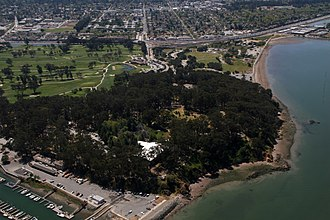 Coyote Point Park - Coyote Point from the air. Peninsula Avenue retreats into the center background after crossing Bayshore Freeway (US 101), which runs from left to right in the upper portion of the picture. The marina, at lower left, runs almost directly north-south. Beyond the trees, in the upper left, is the adjoining Poplar Creek Golf Course.
