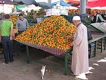 Un stand avec des oranges, un homme à côté de lui, un chat sur le plancher