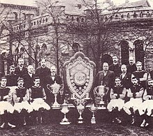 A sepia photograph with a large old structure in the background obscured by trees. In the foreground there is a large shield surrounded by five trophies. On either side of the shield stand 8 people.