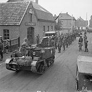 A Bren Gun Carrier brings in a batch of German prisoners