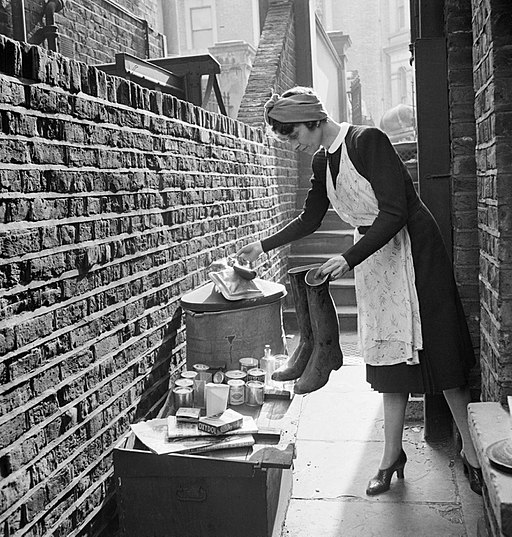 A British housewife puts out items for salvage during 1942. D7560
