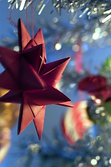 An out-of-focus close-up of a part of a Christmas tree with glitter garlands and blurry decoration. In-focus in the left half of the picture, suspended from one of the twigs, is a red cardboard-woven Froebel star. Four tips and seven prongs are visible.