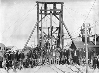 Gold mining in Nevada - A group of miners pose in front of mine headframe in  Goldfield  ca.1905