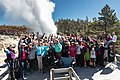 A group of people pose for a photo during the steam phase of a Steamboat Geyser eruption (44068753794).jpg