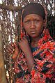 A young woman waits to receive UK-funded food aid in Dolow, Somalia, 28 January 2012 (6925380399).jpg