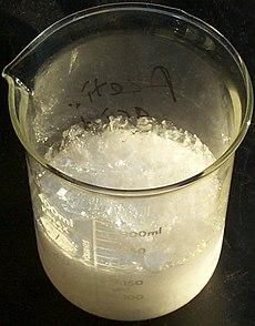 glass beaker of crystallised acetic acid