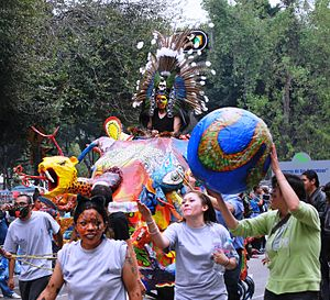 Mexico City Alebrije Parade - Participants pulling one of the alebrijes ridden by participant in Aztec costume