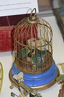 Antique wind-up toy bird in a cage (25883515096).jpg