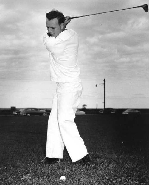 Arnold Palmer in the coast guard swinging a golf club
