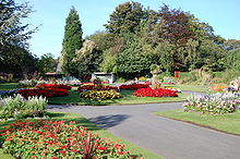 Pathway leading towards a circular flowerbed where the path splits. Flowerbeds also flank the path on each side. The flowerbeds are decorated by various red and yellow flowers. Trees are in the background.