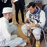 Astronaut John W. Young checks over his helmet.jpg