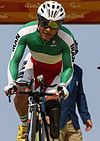 Male cyclist in the Uniform of the Iranian Paralympic Team riding a bicycle