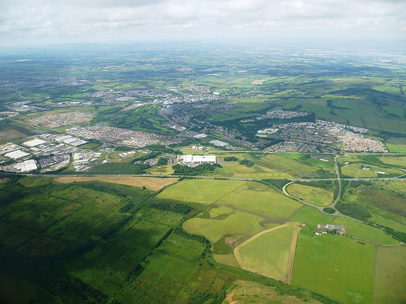 View of Bathgate, West Lothian from an aeroplane approaching Edinburgh Airport. The town can be seen on the north side of the M8 motorway with the Whitehill Industrial Estate on the left, the Pyramids Business Park in the centre and Boghall on the right.