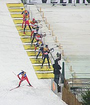 Several biathletes in the shooting area of a competition