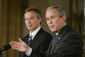 George W. Bush answering a reporter's question during a joint press availability with Prime Minister Tony Blair in the East Room of the White House, July 28, 2006. White House photo by Paul Morse