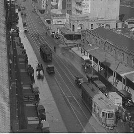 View down street with cars and trams