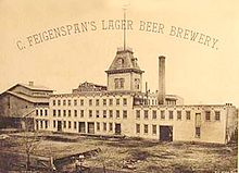 "A black and white image of a factory with a steeple, a smokestack, and the caption ""C. Feigenspan's lager beer brewery."""