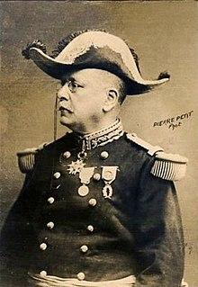 Fotografia monocromática de um homem sentado, de perfil, vestindo roupa de general e chapéu armado.