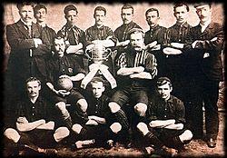 Malnova teamfoto, kun ludantoj ĉirkaŭ trofeo