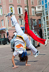 Two Croatian practitioners of the Brazilian martial art capoeira in the middle of doing a cart wheel on a public sidewalk.