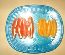 Slices of common and cara cara oranges on a plate.