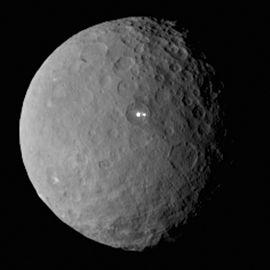 Photographie de Cérès prise par la sonde Dawn en février 2015 montrant des points lumineux de nature inconnue.