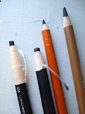Two charcoal pencils in paper sheaths designed to be unwrapped as the pencil is used and two charcoal pencils in wooden sheaths.
